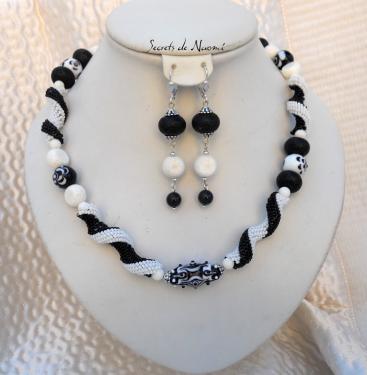 Collier noir et blanc composé de perles tissées, de perles filées au chalumeau j'ai tissé les perles avec des rocailles noir et blanc mat, et ajouté des perles en lave et en corail blanc. Le fermoir est de couleur argent.  Le collier mesure 50 cm. Les boucles mesurent 5 cm.   Cette pièce est unique.  Voici un bijou facile à porter avec la petite robe noire ou blanche ?