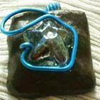 OEIL BLEU:Pendentif en p�te fimo marron vernie, sur�lev� d'un galet transparent bleut� en forme d'�toile, entour� d'un fil d'aluminium bleu, qui permet de passer le cordon. Cordon en plus pour 0,50cts