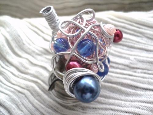 bague r�glable en fil d'aluminium argent� qui tortille sur une boule en fil de cuivre et parsem�e de pierres nacr�es bleues,rose et rouge