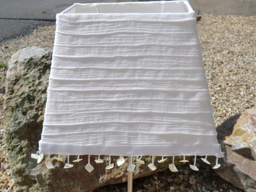 Abat-jour réalisé en Voile de coton doublé souligné d'un ruban blanc satiné aux franges de perles transparentes et carré de Nacre naturelle. Prix unitaire Hauteur 23 cm - Largeur 30 cm - Profondeur 20 cm  Forme Pyramide - Culot E27 réducteur sur demande