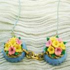 Collier sur fil en cuir bleu accroché à des capsules de bouteille peintes et vernies et décorées par des fleurs en pâte fimo. Les deux capsules sont reliées par une chaîne en métal doré