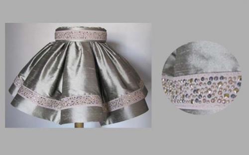Confectionné dans une jolie soie grise et rehaussé d'un galon de strass, cet abat-jour est doublé d'un pongé de soie de couleur en harmonie avec la jupe.