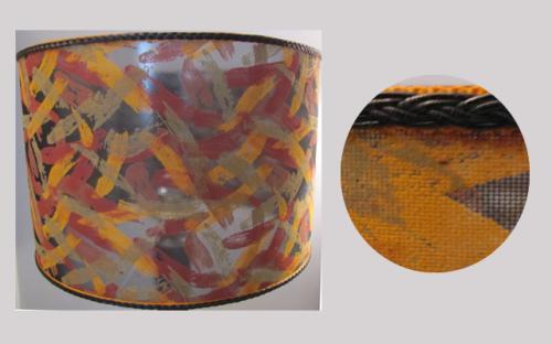 Cet abat-jour cylindrique est réalisé dans une matière synthétique transparente avec des tons de jaune orangé, pourpre et noir qui laisse filtrer une jolie lumière d'ambiance. Il est agrémenté d'une double soutache haut et bas de couleur orange et noir. Sur un pied de lampe en bois des années soixante, l'ensemble révèle un style rétro.