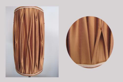 cet abat-jour de forme cylindrique est confectionné  dans une soie de chez edmond petit doublée et agrémenté de fines perles permettant le froncage du tissu lui donnant cet effet smock. Une soutache (haut et bas) dans les tons bois de rose vient rehaussé l'ensemble.