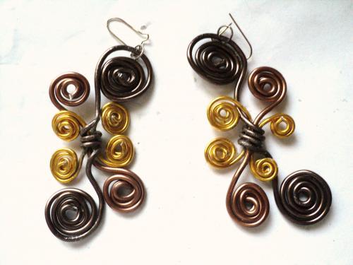 Boucles d'oreille pour oreilles perc�es,fabriqu�es avec du fil d'aluminium de trois couleurs;chocolat,marron et dor� qui enroul� pour faire des tortillons de tailles diff�rentes