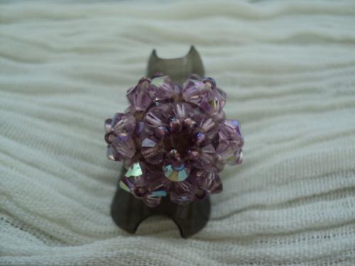 VIOLETTE Bague en perles sur anneau r�glable en m�tal argent�,la base de cette bague est form�e de facettes et de rocaille violettes. La fleur est compos�e de six carr�s de toupies violettes, surmont�es de rocaille. Le centre de la fleur forme un cercle de six toupies surmont�es de rocaille. Cette bague �tincelle de mille feux et � un tr�s bel effet.  Elle convient parfaitement aux amoureux des belles pierres et de l'�l�gance.