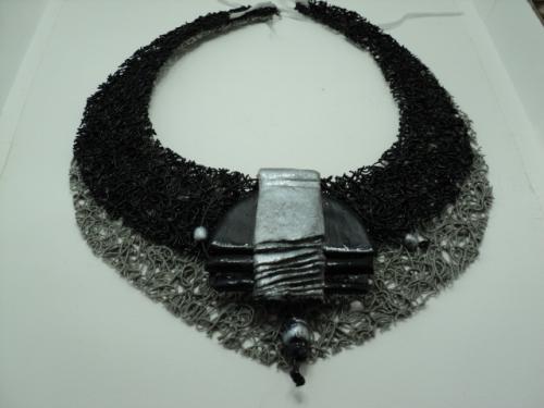 Collier en plastique tissé noir et gris, fermé par un ruban gris. Le devant est décoré par un pendentif en pâte fimo noir et gris