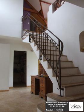 Rampe d'escalier en fer forgé, tous les noyaux et les volutes sont réalisés dans les règles de l'art. La rampe a été rouillée puis vernie. La main courante descend suffisamment pour accompagner la personne jusqu'en bas.