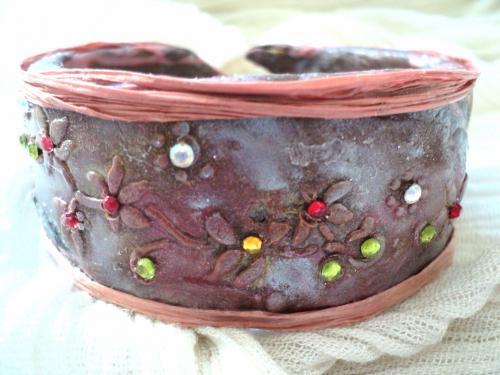 Bracelet en p�te fimo ,d�cor�e par des poudres de couleur vari�e et des petits strass coll�s,les bords sont rehauss�s d'un cordon en raffia couleur saumon