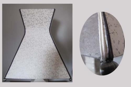 De formes géométriques, cet abat-jour pyramidal à col est réalisé en papier japonais contrecollé. Deux faces en monochrome et deux faces marbrées gris et blanc. Chaque arête est agrémentée de soutaches dans les mêmes tons et d'une bille de fil noir.