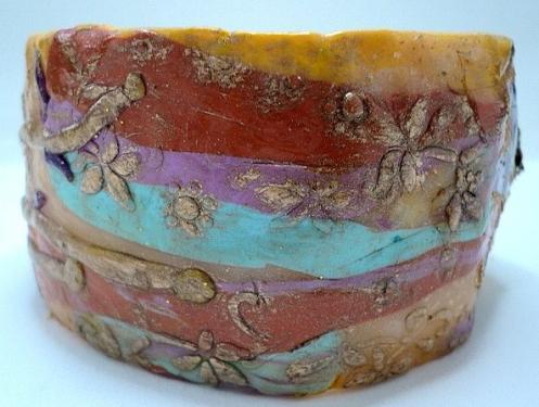 MAR DEL SOL:Bracelet fabriqué à partir d'une grille fine en aluminium, entièrement couverte de pâte fimo jaune.Ce bracelet est décoré avec des bandes de pâte fimo de plusieurs couleurs, de motifs sculptés dans la pâte et dorés à la cire. En ses extrémités deux fleurs, une de pâte fimo transparente laissant apparaître des feuilles d'or, entourée de paillettes dorées, et d'un sequin bombé mauve en son centre. L'autre fleur est fabriquée en pâte fimo mauve et bleue clair,entourée de paillettes dorées surmontée en son centre d'une fleur en métal argenté dont le coeur est décoré d'un strass rose. Le tout est verni. Bijoux très très original et unique.