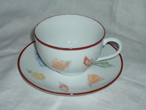 Tasse et sous tasse ornées de fines plumes colorées.