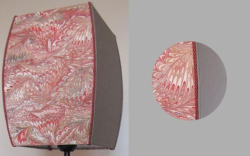 Abat-jour bombé  dont deux faces sont réalisées en papier marbé et deux faces en taffetas de soie grise. Sur un pied métallique l'ensemble donne une ligne très apurée et contemporaine.