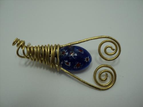 SPARTACUS: Broche en fil d'aluminium torsadé, perle en verre de Murano bleu, décorée avec des petites fleurs rouges et blanches. Fermoir sur épingle argentée, avec système de sécurité.