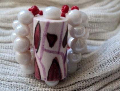 CALIENTE: Bague taille 57-58 compos�e d'une grosse perle en c�ramique blanche et rouge. Le tour du doigt qui fait corps avec la perle est fait de petites perles en c�ramique blanche et de rocaille rouge
