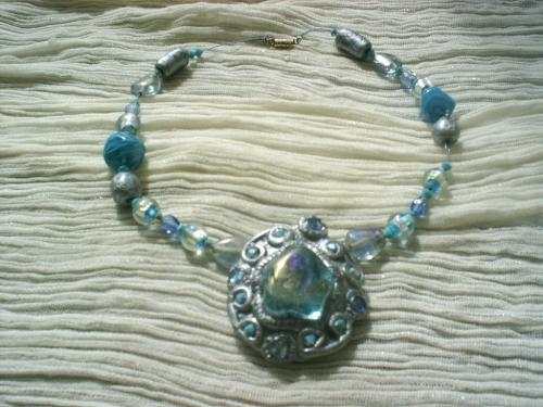 PRECIOSO: Collier sur fil câblé bleu,enfilade de perles de verre de bohème bleu, perles indiennes bleues, et feuille d'argent, perle en pâte fimo grise, au centre un médaillon en pâte fimo grise vernie dont le coeur contient un galet transparent irisé bleu et entouré de facettes bleues. Fermoir à vis