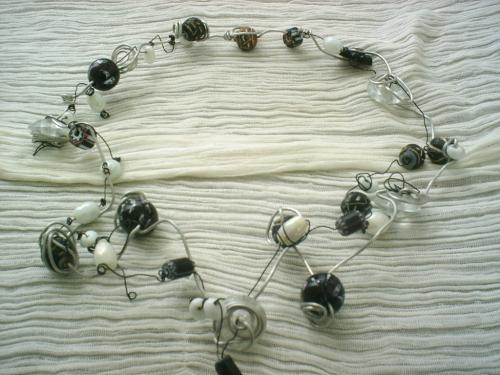 BATNA:Collier en fil d'aluminium argenté et fil de cuivre noir. Le collier est composé de perles noires et blanches de tous les genres et toutes les matières: porcelaine,verre,bois,et de toutes les formes: rondes, ovales,cylindre aplati.