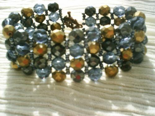 CHICOS:Bracelet tissé avec des facettes de 6 mm noires, gris transparent et dorées, intercalaire de petites facettes en cristal de swaroski grisées, le tout sur fil de nylon, fermoir balance bronze.     Longueur 20 cm.