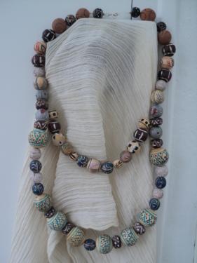 Collier composé de perles en bois peintes à la main et terra cota de tailles différentes, plus petites pour le deuxième rang. Fermoir mousqueton. Longueur:35cm
