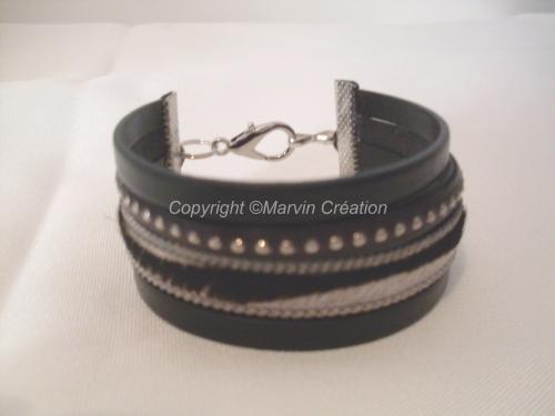 Bracelet manchette (19 cm avec fermoir), 4 liens en cuir plat 2 couleur noir, 1 imitation peau de vache et 1 cuir clouté , fermoir mousqueton. Réf: BRA04163