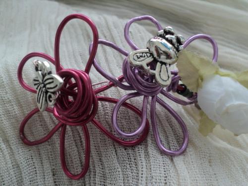 FLEURETTE:bracelet enfant en fil d'aluminium fuchsia et rose pâle, en forme de fleurs. A droite de la fleur fuchshia, une fleur blanche en tissus et un petit coeur en métal argenté.Chaque fleur est butinée soit par un papillon soit par une abeille, le bracelet s'adapte à toutes les tailles de poignet grâce au fil d'aluminium.