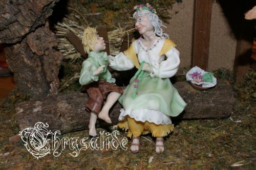 Edora et Ethan sont entièrement modelés en porcelaine froide à la main, sans moule. Ce sont des modèles uniques. Ils sont fixé sur une branche de bois coupée et dont la base est recouverte de feutrine. L'ensemble de la scénette mesure approximativement 25 cm de long * 15 cm de haut et * 9 cm de large. Ils ont été photographiés dans une crèche disponible pour 15? Voici EDORA la doyenne de la communauté elfique de mon jardin. Chez les Elfes, chacun a une tâche à accomplir pour le bon fonctionnement ou le bien-être de la communauté. Edora s'est vu confier la confection des couronnes de cérémonies. Elle tresse de grandes herbes souples qu'elle va cueillir au cours de ses longues promenades méditatives, et elle y fixe lierre, fleurs ou fruits selon la saison. Chaque Elfe porte une couronne qui symbolise sa fonction au sein du groupe. Edora est la gardienne de ces traditions et de ces savoirs. De mémoire d'Elfe, nul ne sait quel est son âge... elle a toujours été là. Douce, disponible, toujours à l'écoute, elle est la confidente de tous, celle vers qui l'on se tourne pour demander conseil, confier ses secrets ou simplement ouvrir un peu son coeur. Aujourd'hui c'est Ethan, le cousin d'Aaron, qui est à ses côtés. Que lui raconte-t-il? Quel secret, quelle requête, quelle aventure? Seule Edora pourrait le dire mais elle ne le fera pas car, avec elle, les secrets sont bien gardés. Les parents de la tribu sont en confiance, ils savent qu'elle saura guider leurs petits avec sagesse et bienveillance. Matériaux utilisés : Bois Porcelaine froide