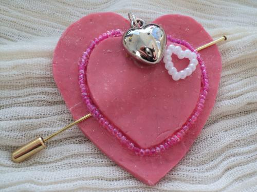 Broche en pâte fimo rose en forme de coeur et torque en métal doré. Le coeur est décoré de deux petits coeurs un en plastique blanc et un en métal argenté