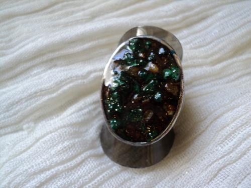 judith:Bague sur support en métal argenté, décorée d'éclats de minéraux verts et orange, enfermés dans une coque en résine. Cette bague a un rayonnement très spécifique la lumière éclaire les pierres vertes, et fait briller les autres pierres d'une couleur ambre, le tout brille d'un éclat satiné grâce à la résine; Anneau réglable.