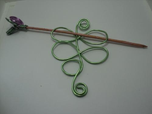 LYS: Pic à cheveux composé d'un pic en bois dont le bout est décoré par deux tortillon un rose et un vert. Le corps du pic est en aluminium vert.Il peut être positionné horizontalement comme verticalement