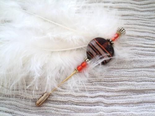 Broche ou pic à chapeaux en métal doré. Fibule décorée avec une magnifique perle marron-orangé,des facettes oranges,des perles en métal doré,et une plume blanche.
