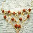 ROSALINDE: Collier en fil d'aluminium dor� tiss� en grosse maille et parcouru de perles en plastique rouge et beige d�cor�es de fleurs