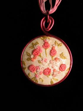 Collier avec médaillon brodé dans un camaieu de roses,  lacet en coton ciré et organza. Diam 40mm