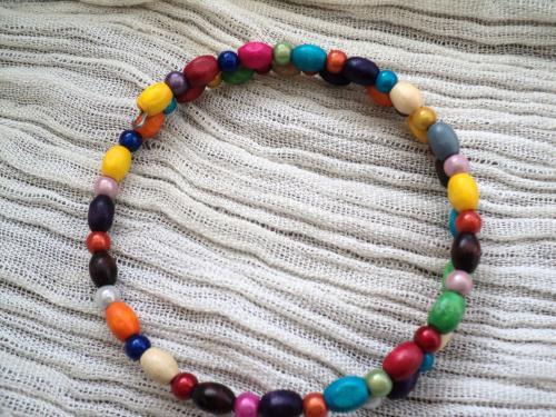 Petit bracelet mémoire deux tours en métal argenté.Les perle sont en bois et multicolores bracelet pour femmes et adolescentes