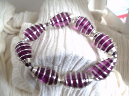 Bracelet sur élastique,composé de huit cages en fil d'aluminium argenté garnies de perles en verre mauve. Ce bracelet très lumineux, peut s'adapter à toutes les tailles de poignet adulte.