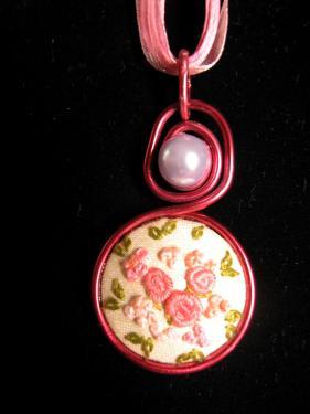 Collier avec médaillon brodé dans un camaieu de roses, perle cirée en décor et lacet en coton ciré et organza. Diam 30mm