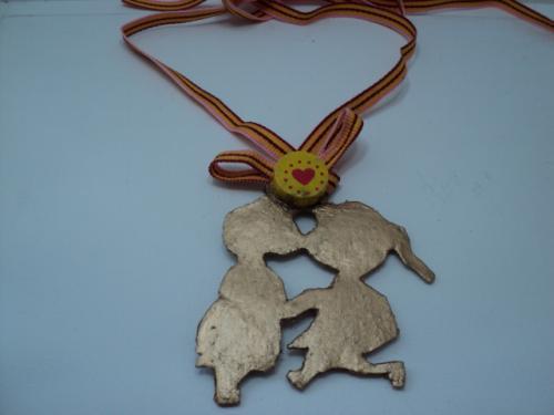 AMOURETTE:Pendentif en pâte fimo très très fine,peinte en or, cirée à la cire d'or et vernie.Les deux personnages sont surmontés d'une perle en bois jaune, décorée de pois et coeur rouge. Un ruban rayé,rose,jaune et rouge, permet d'ajuster la hauteur du pendentif à la longueur désirée. Le petit plus ce pendentif peut-être porté par une petite fille ou par sa maman.