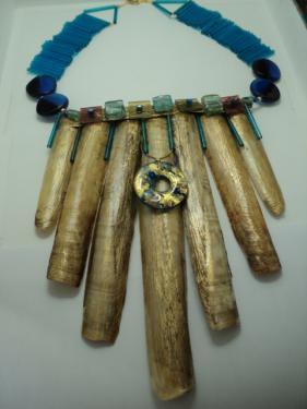 Coquillages cirés à l'or et vernis. Un  pendentif bleu et or pend sur le devant.Le haut est décoré avec des carrés en verre et des facettes bleues. Le tour de cou est en perles allongées  en verre bleu