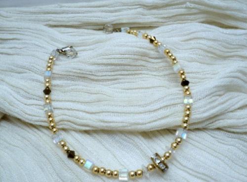 FINESSE DOREE:Bracelet très fin , qui peut aussi servir de chaîne de cheville.Ce bijoux est monté sur un fil d'aluminium, il est composé de petites perles dorées, de toupies couleur mocca, de petits cubes blanc opale, de petites fleurs transparentes et en son centre d'une rondelle strassée blanche sertie dorée. Le fermoir est à visser il est encadré de deux facettes transparente de 6mm. Longueur totale 22 cm Ce bracelet est très chic de par sa finesse et ses éclats lumineux.