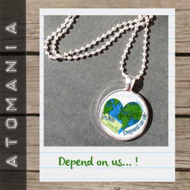 Pendentif « Depend on us »  - ATOMANIA  composé  d?une image créée par « Atomania », protégée par résine transparente, montage sur support argenté ? chaîne assortie (longueur : 60 cms). Format : 25 mm.