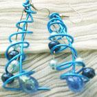 CLOCHETTE:sur crochets argentés pour oreilles percées, spirale de fil d'aluminium bleu, fausses perles de culture bleu clair encagées dans la spirale ainsi que perles en porcelaine bleu foncé et goutte de verre bleu irisé. Longueur 7 cm.