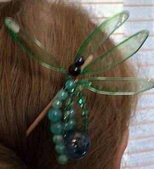 LIBELLULE:Pic à cheveux,monté sur un pic en bois,verni.Le haut du pic est décoré par une libellule en perles mauve, avec des ailes en plastique vert et des paillettes aux extrémités. Quatre branches, décorent ce pic, une en perle de plastique bleu, une deuxième avec les mêmes perles mais qui se termine par une perle en verre bleu et deux autres composées de perles facette et toupies vertes.