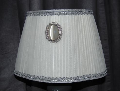 ABAT-JOUR OVALE TRILOBE Magnifique abat -jour ovale trilobe , une forme très chic.  Mousseline de soie, coloris blanc, travaillée en plissé plat .  Doublure gris argent .  Galon Houlès gris argent.  Médaillon ovale en métal argenté avec perle de verre opale.   Convient sur tout type de pied , celui ci est présenté sur un pied fantaisie galet gris .  Bague E27.  Le prix ne comprend pas le pied , me contacter pour l'achat de l'ensemble.   Dimension de l'abat-jour;  Hauteur: 20 CM  Largeur: 32 CM à la base  Profondeur: 20CM à la base.