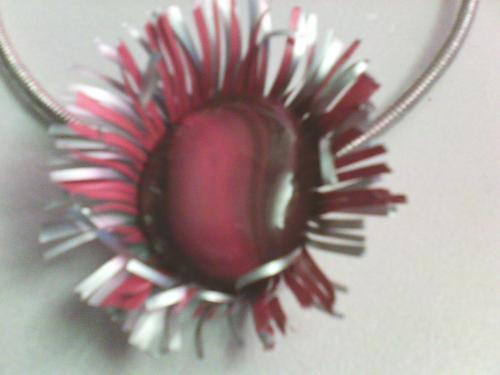 pendentif fleur nespresso ,dont le coeur est une grosse perle de verre rouge/orangée