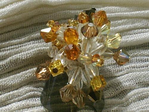 AMBRE Bague sur plateau, anneau réglable doré, base de perles de rocaille dorées, branches sur clous à tête, avec grains de riz en verre transparent, surmontés soit de petites toupies en cristal de swaroski ambre, ou de grosses toupies en cristal de swaroski, jaune transparent, et marron, cube en cristal de sarowski jaune. En son centre 2 poires en cristal de swaroski couleur ambre.     Hauteur totale : 3 cm.