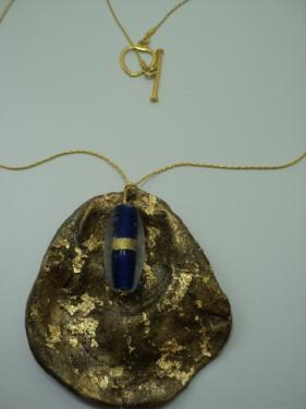 Collier composé d'un coquillage doré à la feuille d'or et verni. Une perle indienne bleue est accroché en haut du coquillage, d'où prt une chaînette fine en métal doré. Fermoir en métal doré