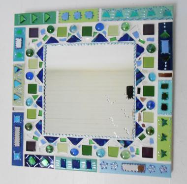 miroir mosaïque 35 X 35 cm   camaïeux de bleus,verts, morceaux de céramique découpée ,billes de verre coloré,petites pâtes de verre turquoises, éclats de miroirs ,émaux, fleurs relief dont le miroir fait 20 x 20 cm.Pièce unique de Odile Maffone fabriquée dans mon atelier en Drôme provençale .a accrocher au mur pour apporter un air de lagon dans votre maison !