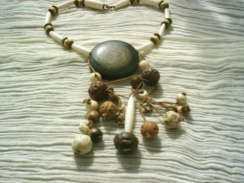 AFRICA:Collier ethnique sur fil câblé. Gros pendentif en émail marron.Tour de cou de perles de bois et terra cotta; Pendant sur coton marron, mélange de perles terra cotta et perles en corne.Fermoir mousqueton bronze. Longueur: 35cm