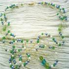 MELI MELO: collier en fil d'aluminium doré enchevêtré et décoré avec des perles de verre etde porcelaine,vert,bleu, blanc, et gris. Fermoir mousqueton doré