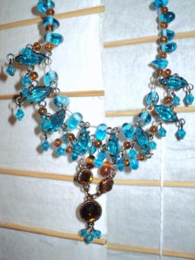 Superbe collier en perles navette de verre bleu séparées par des perles de verre ambre sur le pourtour. La pointe est en perles rondes de verre ambre.
