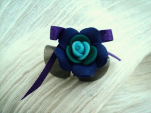Bague sur anneau réglable décorée par une fleur en pâte fimo et un petit noeud en soie.